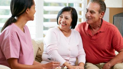 senior couple talking to a caregiver