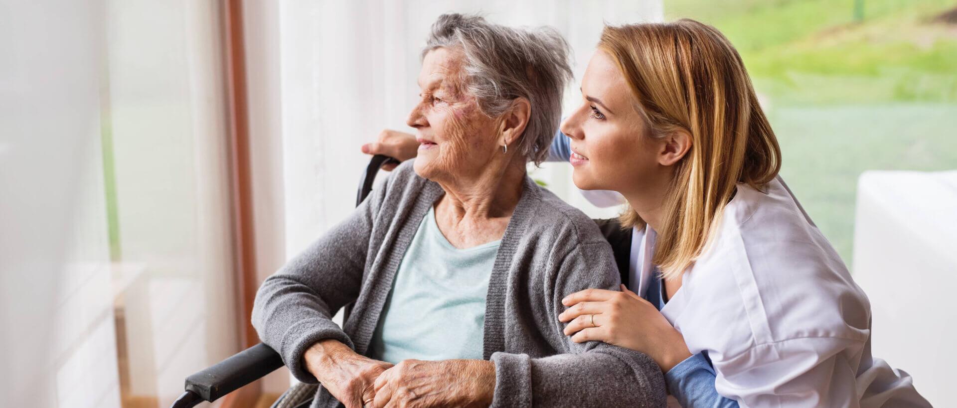 caregiver and senior woman looking at something