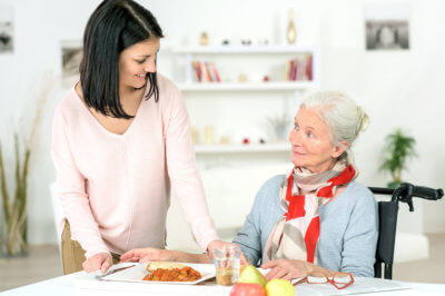 caregiver preparing meal for a senior woman