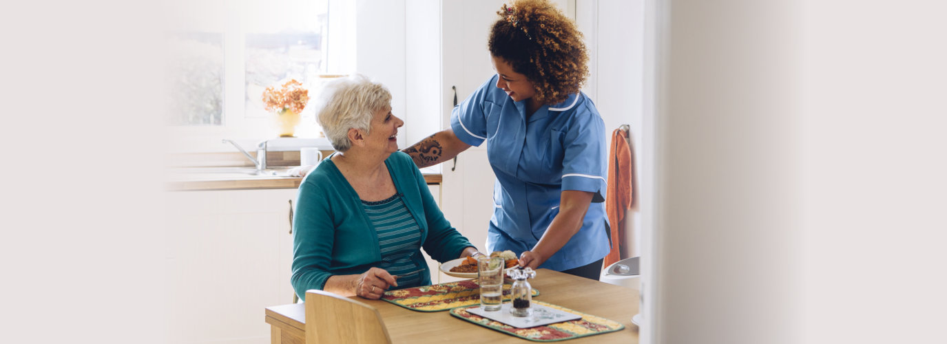 Care worker giving an old lady her dinner in her home